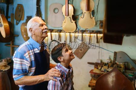 old man grandpa showing guitar to
