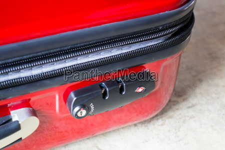 unlock and unzip of red suitcase