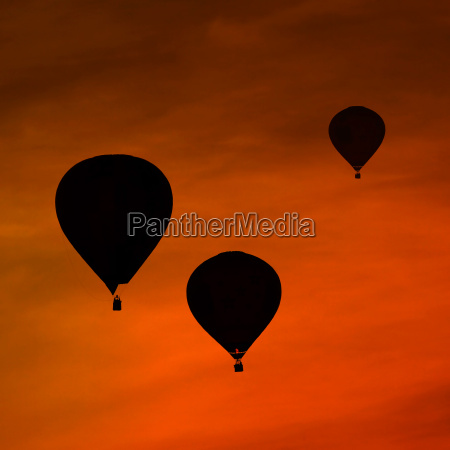 silhouettes of three air balloons in