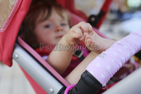 little girl in baby buggy playing