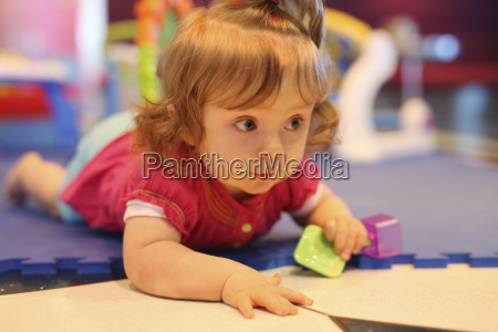 baby girl playing with toys in