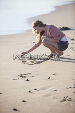 young woman drawing heart in sand