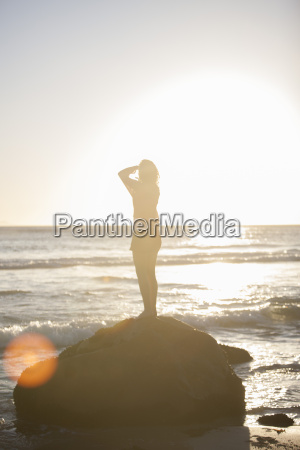 young woman standing on rock on