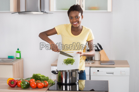 woman putting chopped vegetables in utensil