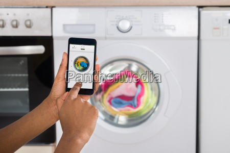 womans hand operating washing machine with