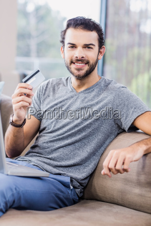 smiling man using laptop and holding