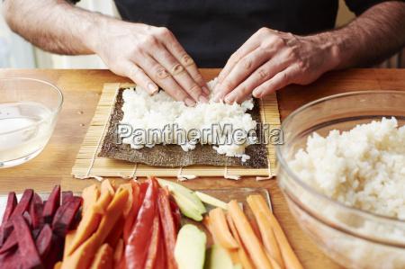 man spreading rice on a nori