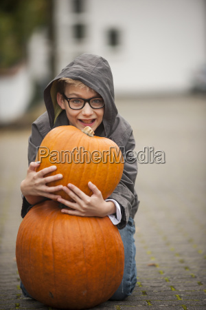 smiling boy with two big pumpkins