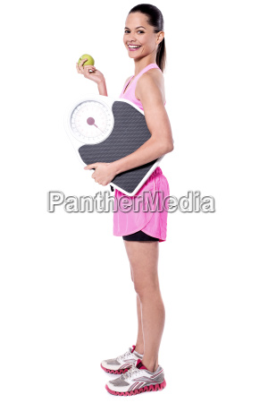 fitness freak woman holding measuring scale