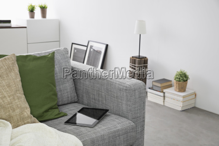digital tablet lying on couch in