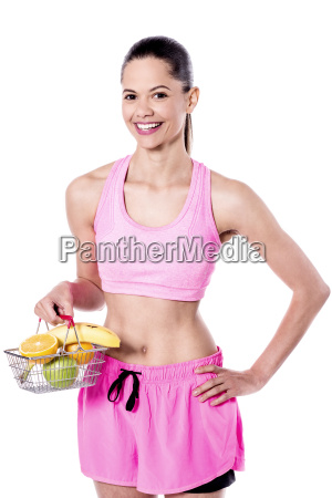fitness woman posing with fruit basket