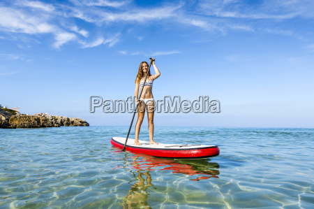 woman relaxing over a paddle surfboard