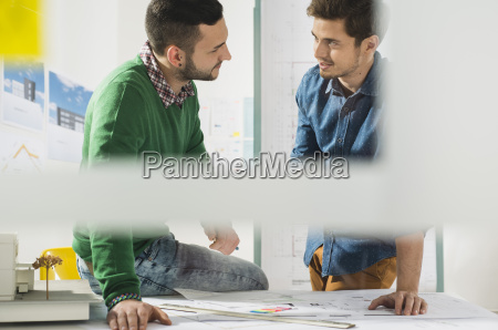 two young architects in office discussing