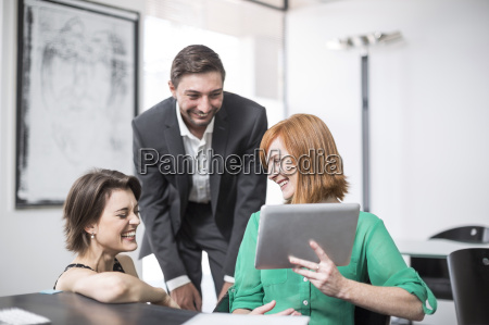 businesswoman showing digital tablet to laughing