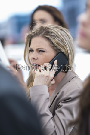 annoyed businesswoman on cell phone in