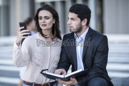 businessman and woman with diary and