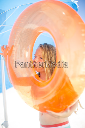girl on beach inflating an orange