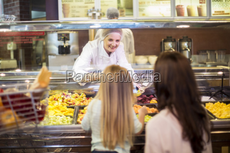 mother and daughter buying fruit salad