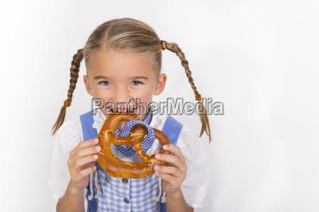 portrait of little girl eating pretzel