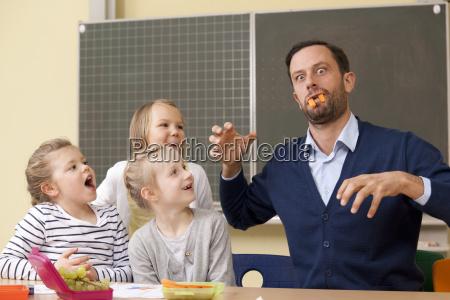 schoolgirls looking at playful teacher wth