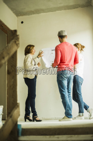architect showing construction plan to young