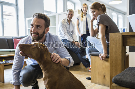colleagues with dog in office