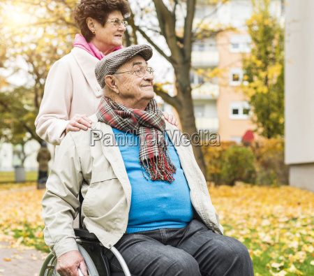 senior woman with husband in wheelchair