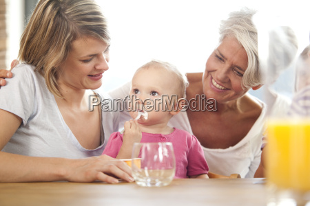 grandmother and mother looking at baby