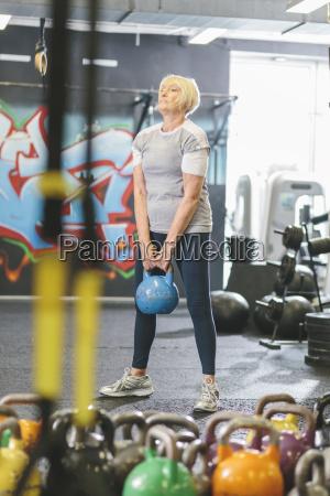 senior woman in gym lifting kettlebell