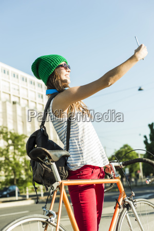 smiling young woman with bicycle on