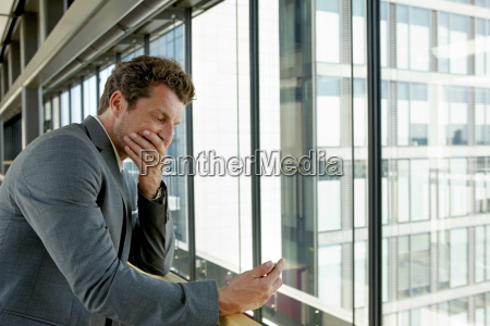 terrified businessman reading text message on