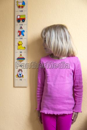 little girl standing beside a yardstick