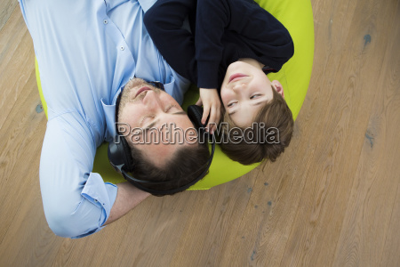 father and son lying on bean