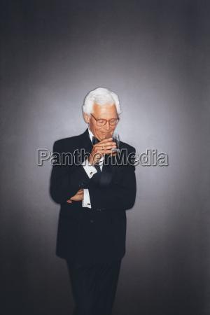 confident elegant senior man drinking from
