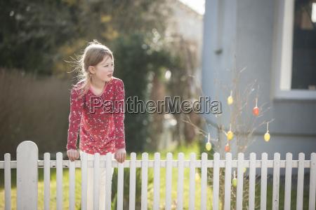 girl at garden fence glancing sideways