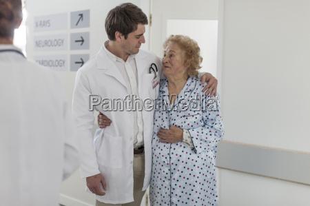 doctor embracing elderly patient on hospital