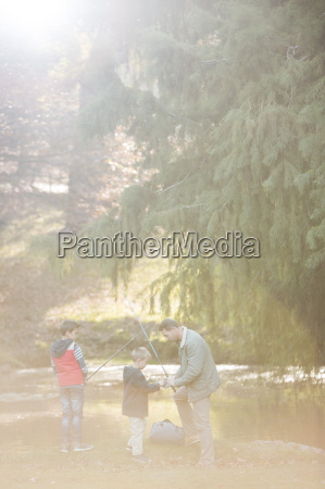 father and sons preparing fishing rods