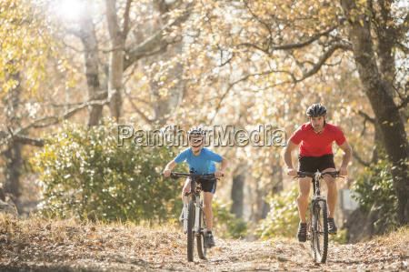 father and son mountain biking on