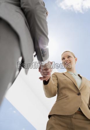 businessman and businesswoman shaking hands under
