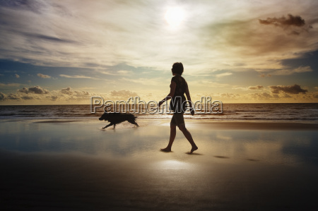 silhouette of woman and dog walking