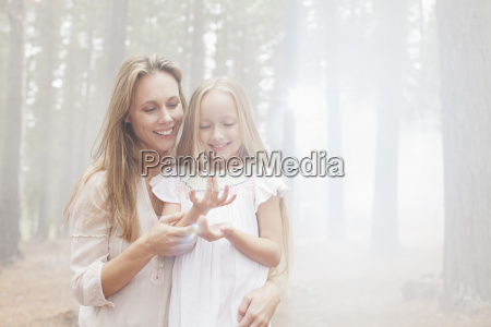 smiling mother and daughter in sunny