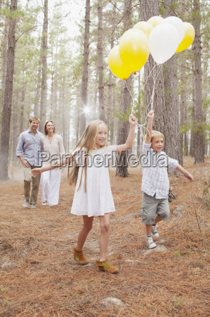 happy family with balloons in woods
