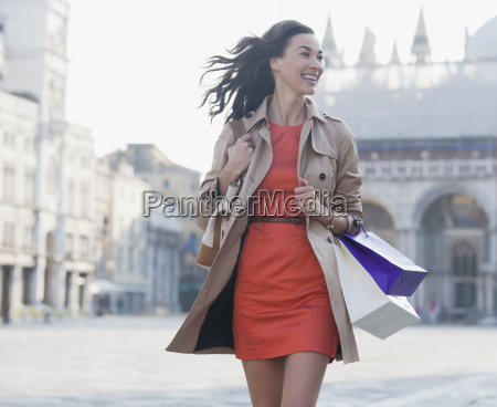 smiling woman with shopping bags walking