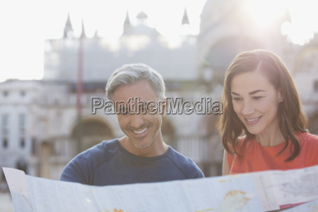 smiling couple looking at map in