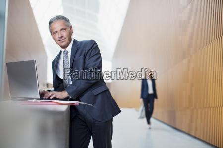 portrait of confident businessman using laptop