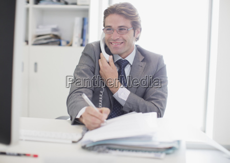smiling businessman talking on telephone and