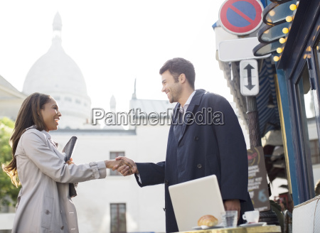 business people shaking hands on city