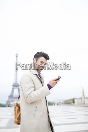 businessman using cell phone by eiffel