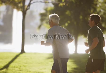 older men jogging together in park