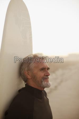 older surfer leaning on board on